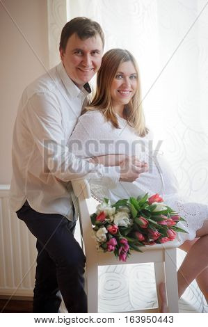 Young man congratulates his pregnant wife. She sits in a beautiful white dress with a bouquet of multi-coloured tulips. Husband tenderly hugs his beloved.