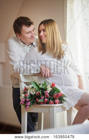 Young man congratulates his pregnant wife. She sits in a beautiful white dress with a bouquet of multi-coloured tulips. Husband tenderly hugs his beloved and lovingly looks at her.