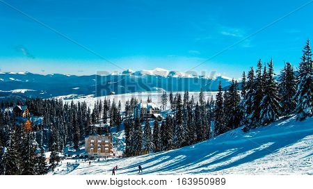 View from the high to the ski resort which attracts skiers on the ski slopes the snow-capped mountain peaks a village in winter mountains