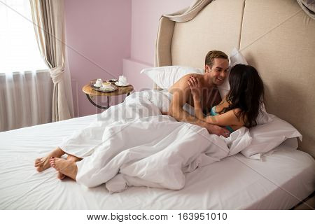 Caucasian couple in bedroom. Man smiling to lady. Time spent together is priceless.