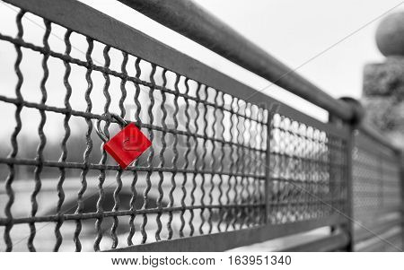 Love lock with heart shape on the bridge as symbol of infinite true love. Black and white retro vintage stock photo with selective red color effect.