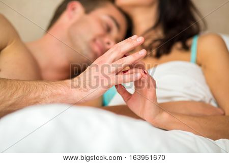 Couple touching hands in bed. Young caucasian woman and man. No one can separate us.