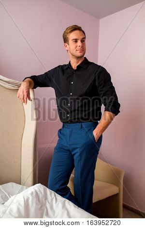 Man is standing near bed. Guy wearing trousers and shirt. Handsome and elegant.