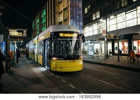 Berlin Germany - December 7 2016. Yellow tram in the evening hour at Mitte Central district of Berlin. Alexanderplatz station.