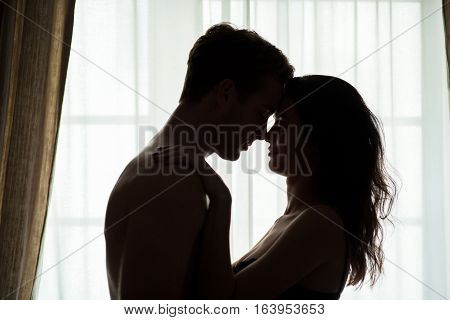 Couple with closed eyes. Woman and man near window. My love is true.