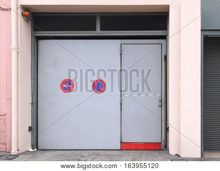 Closed exterior garage door with no parking sign and warning