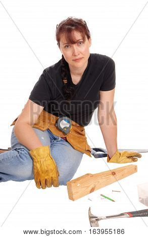 A middle age woman sitting on the floor and working with some tools isolated for white background.