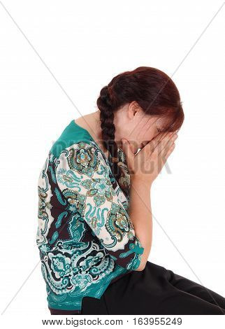 A middle age woman sitting and holding her hands over her face and crying isolated for white background.