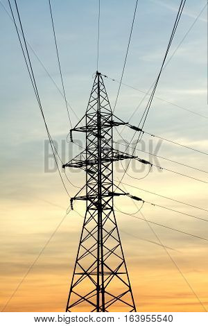 High-voltage power supply line metal tower silhouette on beautiful evening in twilight vertical view