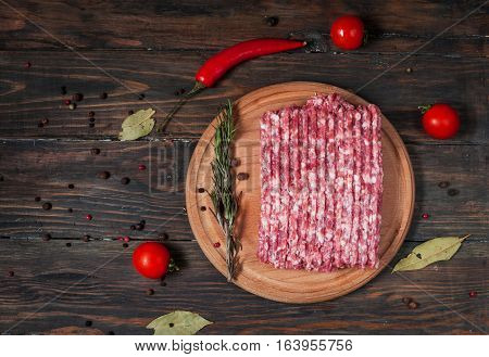 Homemade raw minced meat with herbs closeup top view.