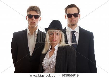 Two young adults in suits and sunglasses behind a woman