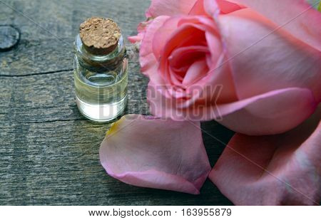 Rose essential oil in a glass bottle with pink rose flower on old wooden table.Rose oil for spa and bodycare.Selective focus.