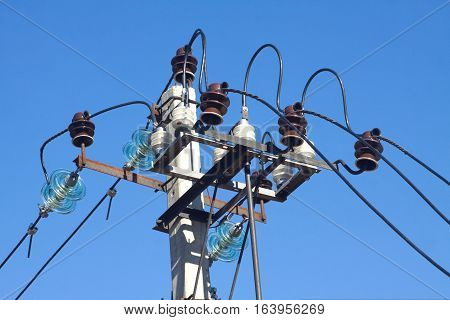 Top section of power line supply prop over blue cloudless sky closeup