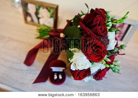 Wedding Bouquet Of Red And White Rose And Ribbon With Wedding Rings On Box