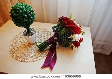 Wedding Bouquet Of Red And White Rose And Ribbon On Table