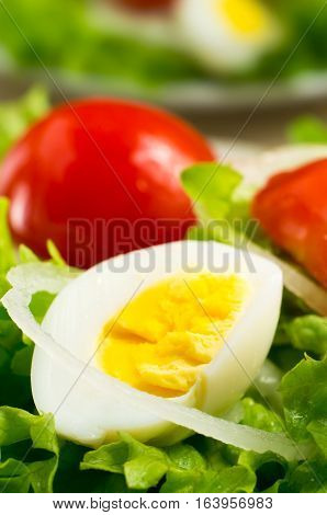 Boiled Egg On A Plate With Lettuce, Onions And Cherry Tomatoes