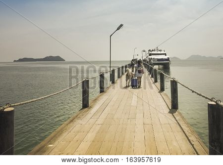 Ferry at the end of pier on Ko Samui island with family walking in foreground Thailand