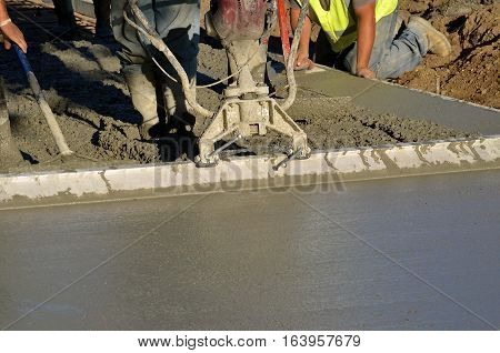 Construction workers screening poured concrete on sidewalk project
