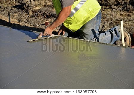 Construction worker troweling wet concrete on a sidewalk project