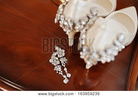Elegancy Wedding Shoes Of Bride With Brilliant Brooch And Earrings On The Wooden Deck.