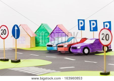 Three paper cars models standing in a row on a parking next to colored houses, in driving school