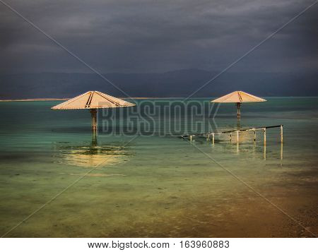 Dead Sea Umbrellas. Storm clouds Dead Sea - bordering Israel, the West Bank and Jordan - is a salt lake whose banks are more than 400m below sea level, the lowest point on dry land. Its famously hypersaline water makes floating easy, and its mineral-rich