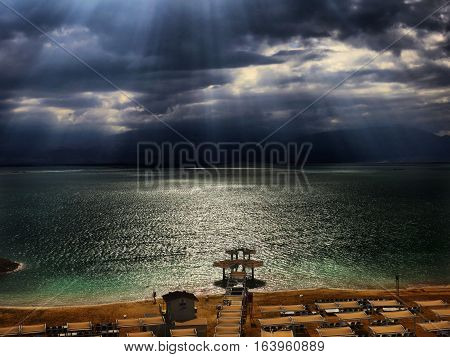 Dead Sea deserted beach. Rays of sunshine breaking through storm clouds at the Dead Sea - bordering Israel, the West Bank and Jordan - is a salt lake whose banks are more than 400m below sea level, the lowest point on dry land. Its famously hypersaline wa