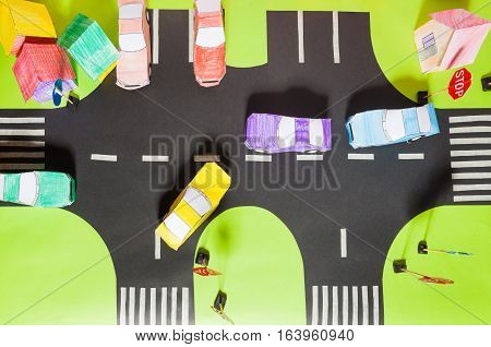 Top view of handmade road traffic with crosswalks, signs, parking and paper toy cars