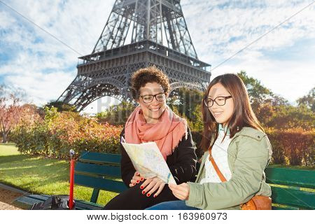 Two happy female tourists looking to traveler guide book on location, sitting on the bench near the Eiffel Tower