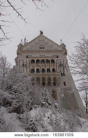 Fussen Germany - December 26 2014: close up view of Neuschwanstein Castle in winter time between trees on December 26 2014 near Fussen Germany.