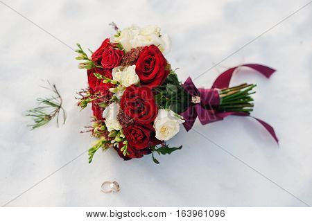 Wedding Bouquet Of White And Red Roses On Snow.