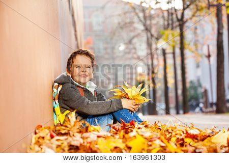 Smiling boy with rucksack  sitting in leaf pile and holding autumn maple bouquet