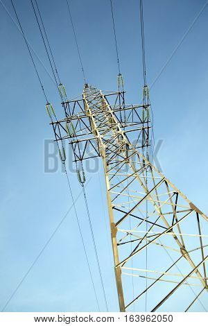 High-voltage power line grey metal prop with many wires vertical view over clear cloudless blue sky bottom-up view