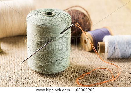 Sewing concept. Thread spool with needle with other spools on canvas background.