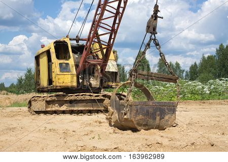 Yellow excavator with big heavy bucket standing on sand on background of forest and cloudy sky on summer day