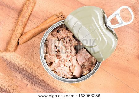 tuna in can on wood plate on wooden background. tuna fish food. Top view
