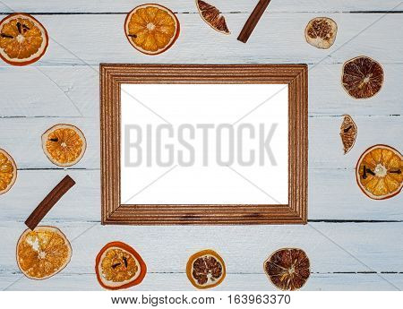 Empty wooden photo frame on white wooden surface among the dried fruit slices