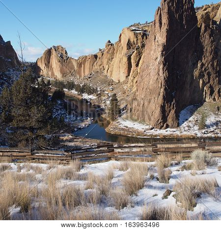 The Crooked River in Central Oregon winds through the formations at Smith Rocks State Park where a fresh blanket of snow is on the ground on a winter day.