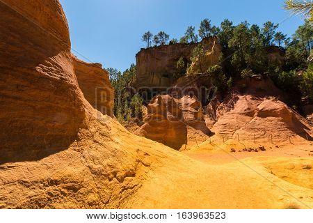 Orange ochre picturesque hills. Luberon, Roussillon Provence France. Preserve natural dye production - ocher.