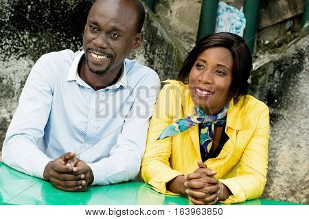 cheerful  young  couple  sitting  outdoors  at a table.