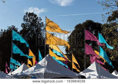 Flags flying atop carnival tents at festival against blue sky