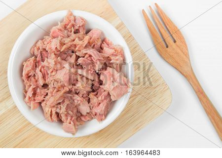 bowl of tuna chunks on wood plate with wood fork on white background.