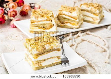 Portion cake of puff pastry with vanilla butter cream. Studio Photo