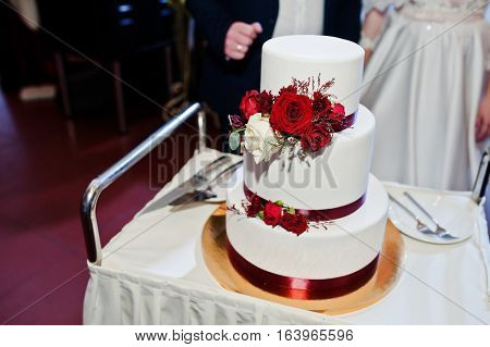 Wedding Couple Cut Wedding Cake With Red Roses And Ribbon