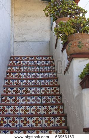 Multi colored mexican tile on steps in a stairwell of an adobe building