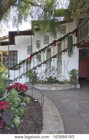 Plaza center with hanging plants and pots on stairs against an adobe wall in Old Town San Diego California