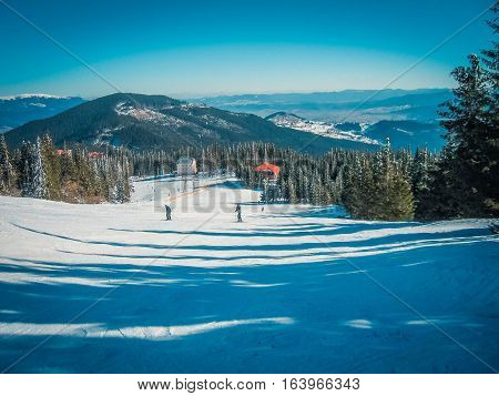 Skiers on the ski resort on a background of snow-capped mountain peaks blue sky and green trees