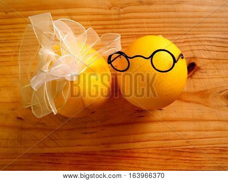 on light wood chopping board are a pair of lovers of yellow lemons boy in dark glasses and a girl with a white bow on a horizontal surface with top view and front