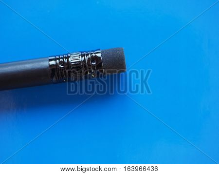 Black Pencil Rubber Over Blue With Copy Space