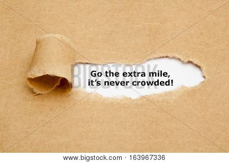 Motivational quote Go The Extra Mile It's Never Crowded appearing behind ripped brown paper.